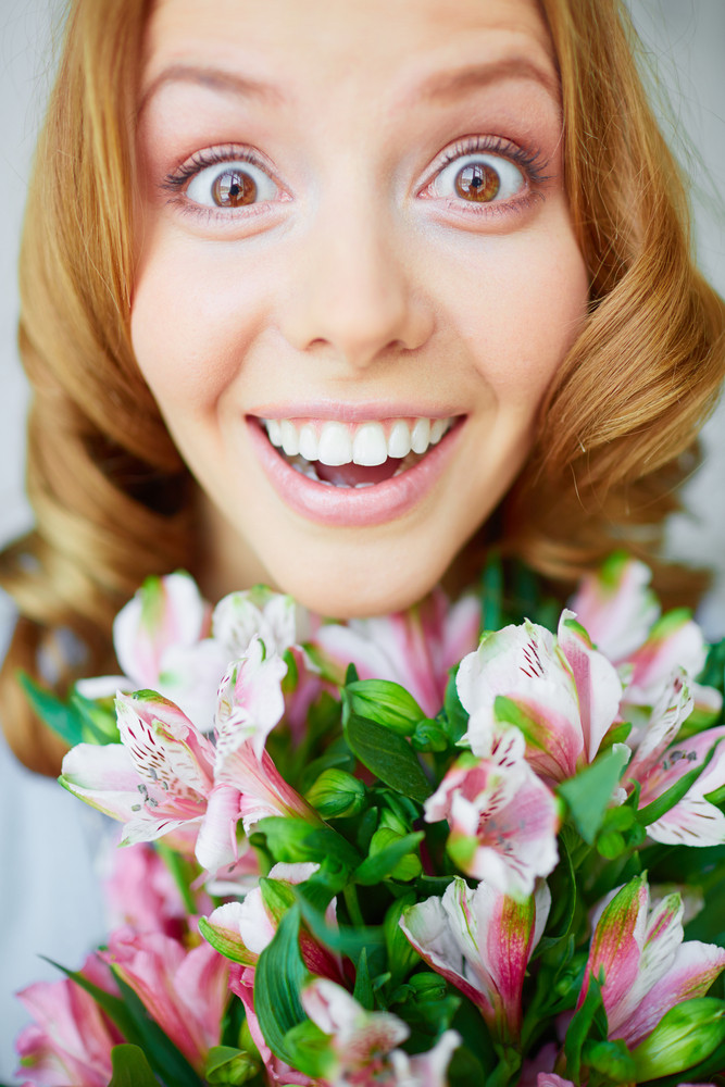 Portrait Of Surprised Female With Bunch Of Pink Lilies