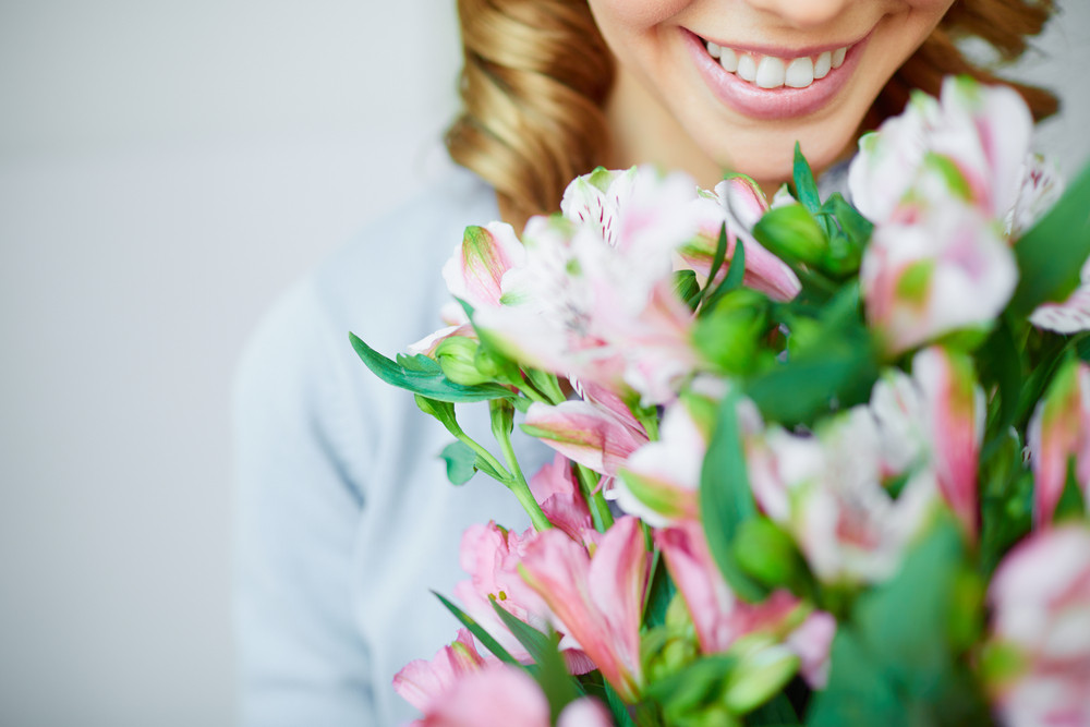 Close-up Of Smiling Female Smelling Pink Flowers