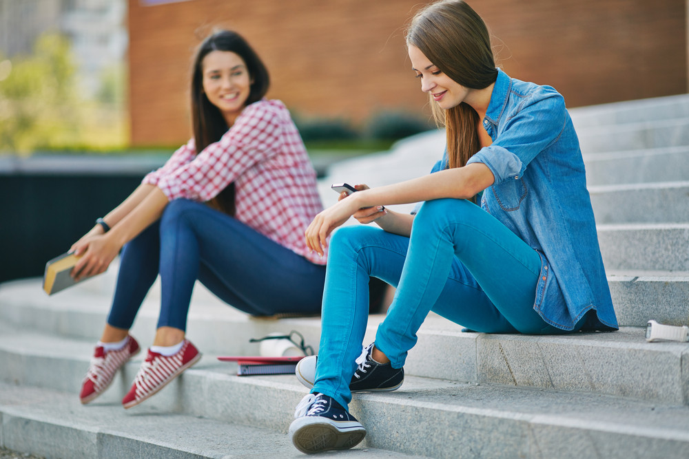 Modern Teenage Student Reading Or Writing Sms While Sitting On Stairs