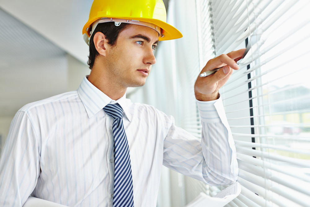 Male Architect In Helmet Looking Through Window