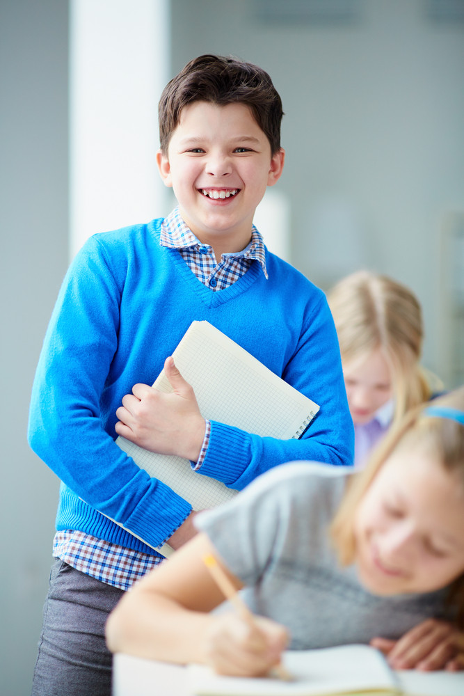 Portrait Of Happy Schoolboy Looking At Camera With His Classmates Near By