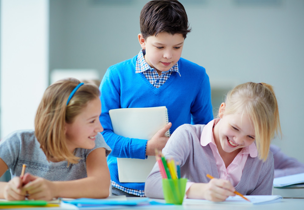 Portrait Of Happy Schoolkids Looking At Girl Drawing At Lesson