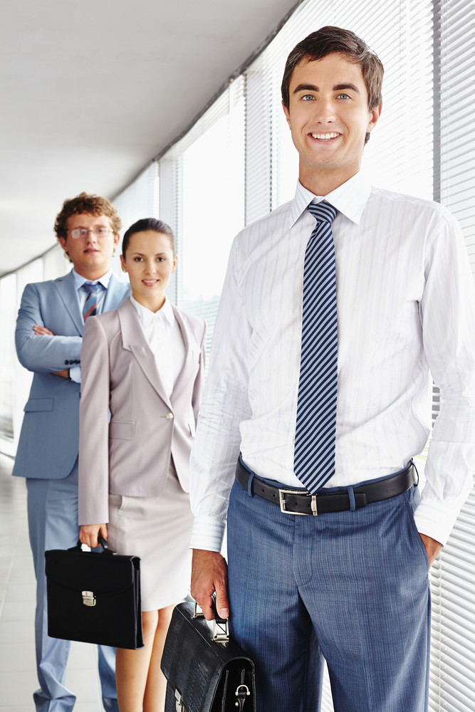 Portrait Of Smart Businessman With Two Colleagues On Background