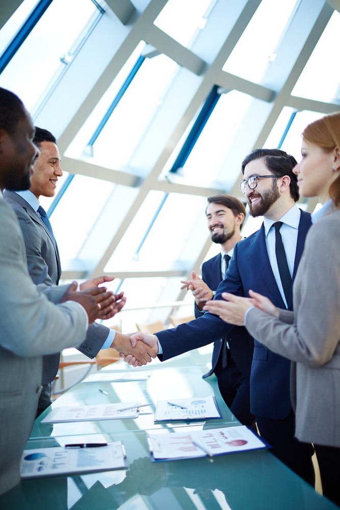 Group Of Business People Congratulating Their Colleagues With Striking Grand Deal