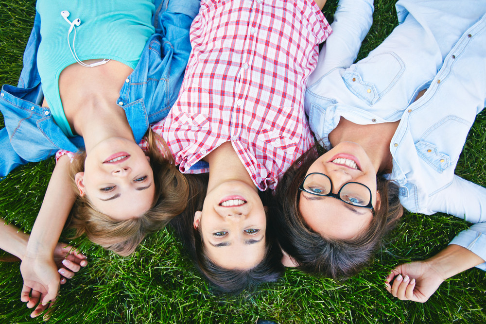 Three Cheerful Teen Girls In Casual Lying On Lawn And Looking At Camera