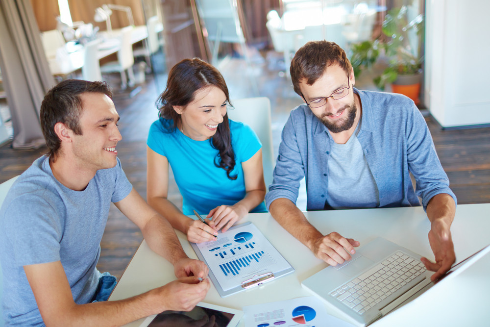Group Of Three Successful Business Partners In Casual Discussing Computer Project At Meeting In Office