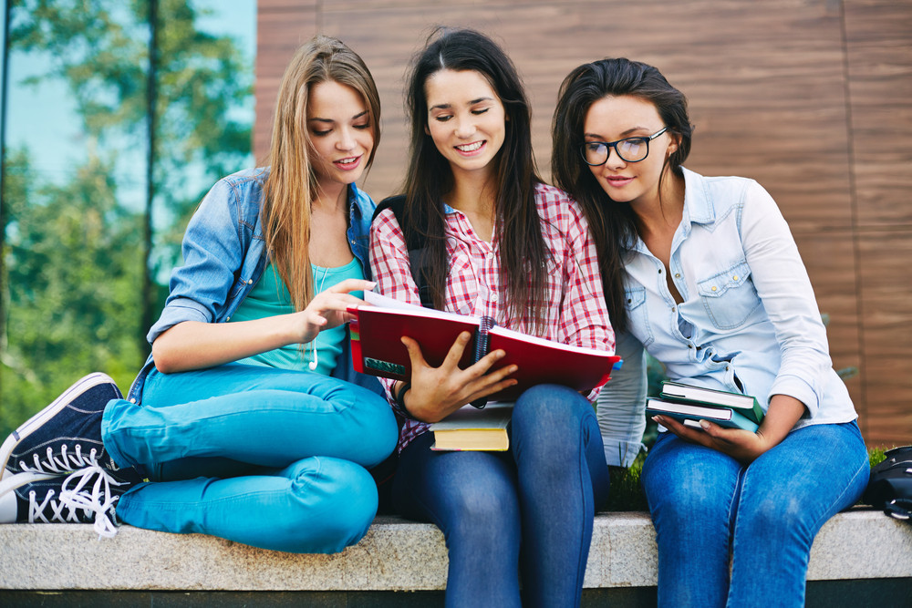 Company Of Happy Teen Girls Reading Book Outside