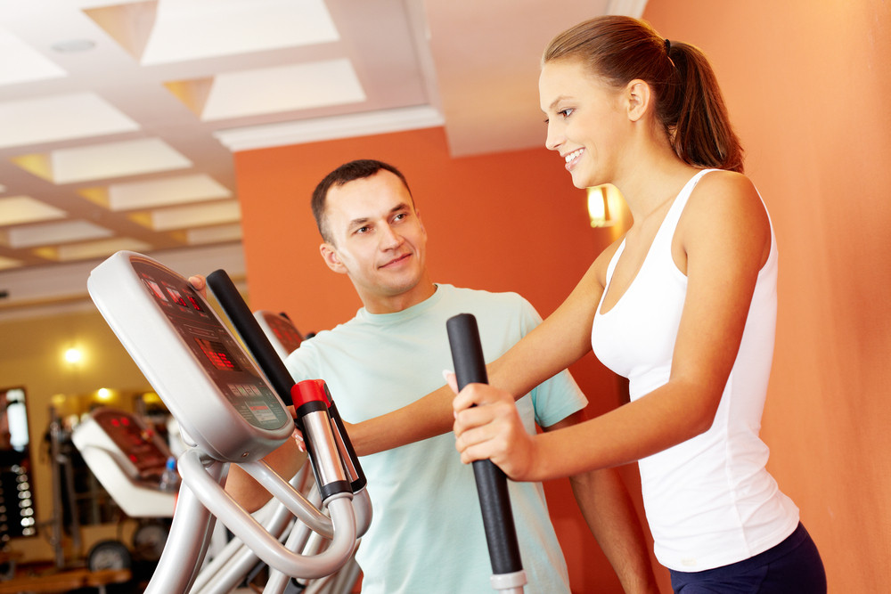 Instructor Showing To A Girl How To Use Treadmill
