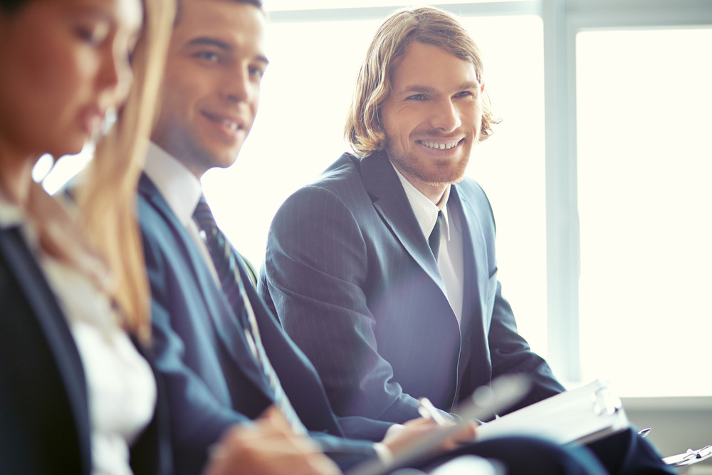 Row Of Business People Sitting At Seminar With Focus On Smiling Young Man