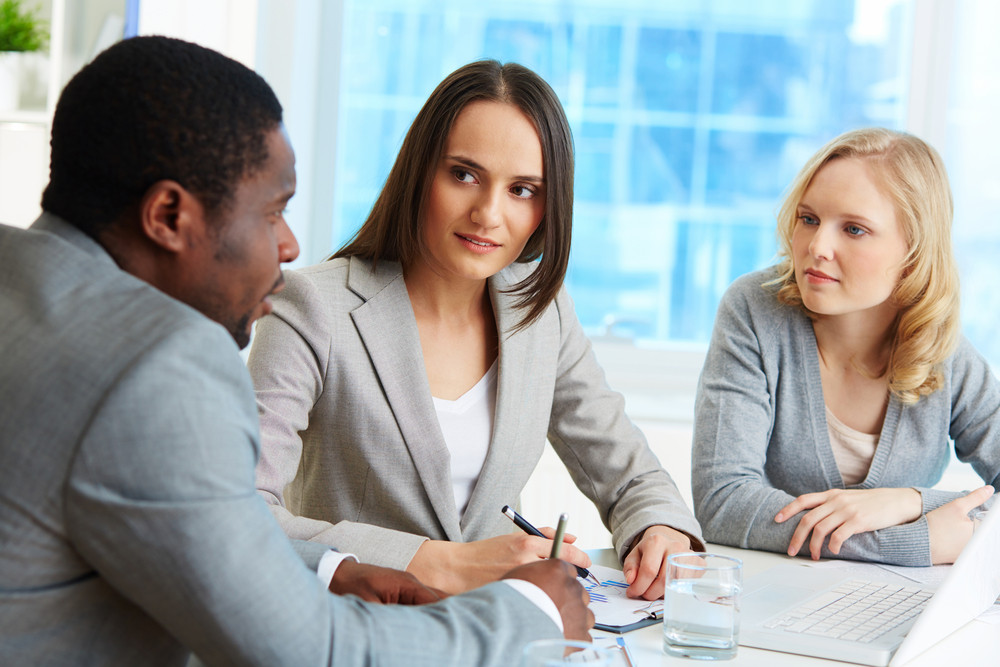 Group Of Friendly Businesspeople Interacting At Meeting