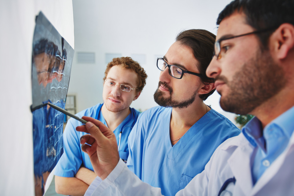 Young Male Doctors Looking At X-ray And Analyzing It