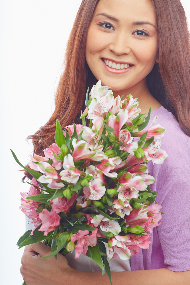 Portrait Of Smiling Female With Bunch Of Fresh Flowers Looking At Camera