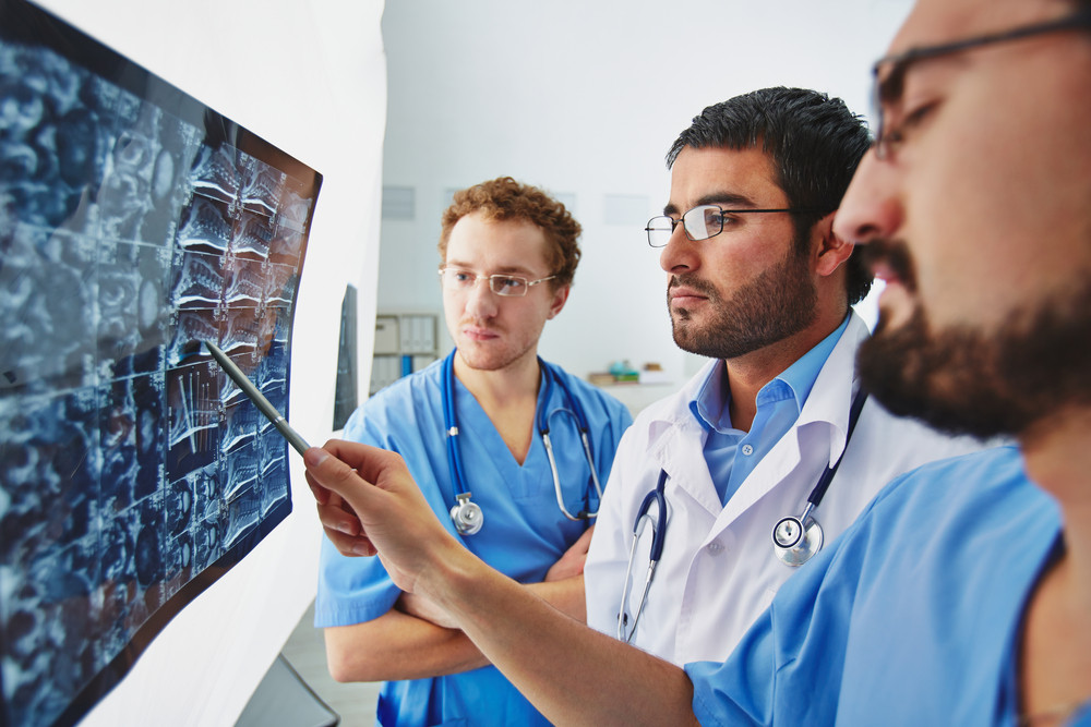 Young Male Doctors Looking Attentively At X-ray And Discussing It