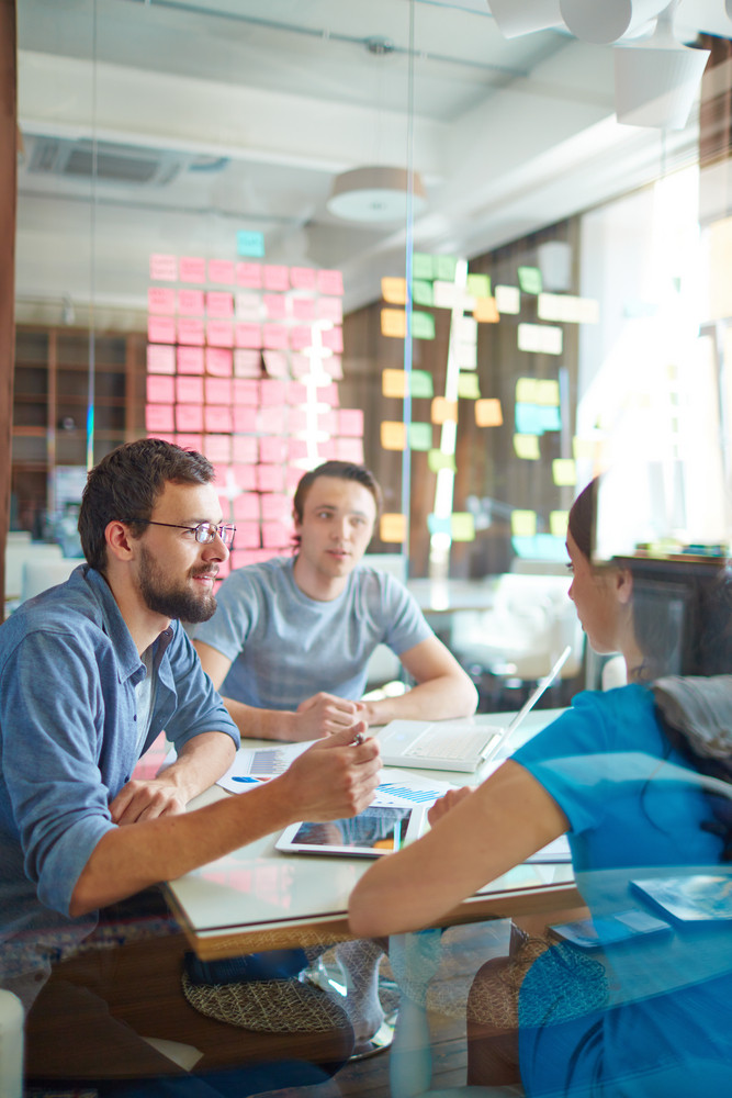 Young Man Explaining Something To His Business Partner At Meeting In Office