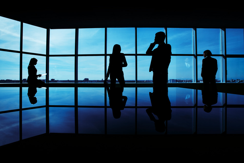 Silhouettes Of Several Office Workers Working On Background Of Window