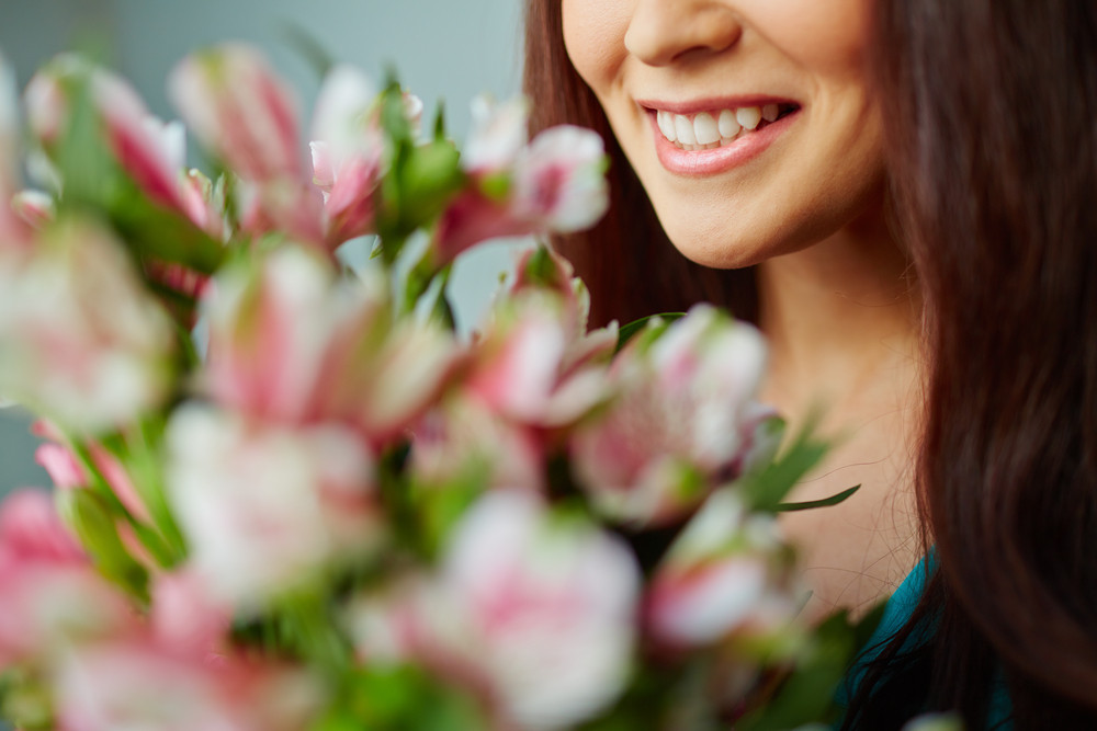 Close-up Of Smiling Female Enjoying Smell Of Flowers
