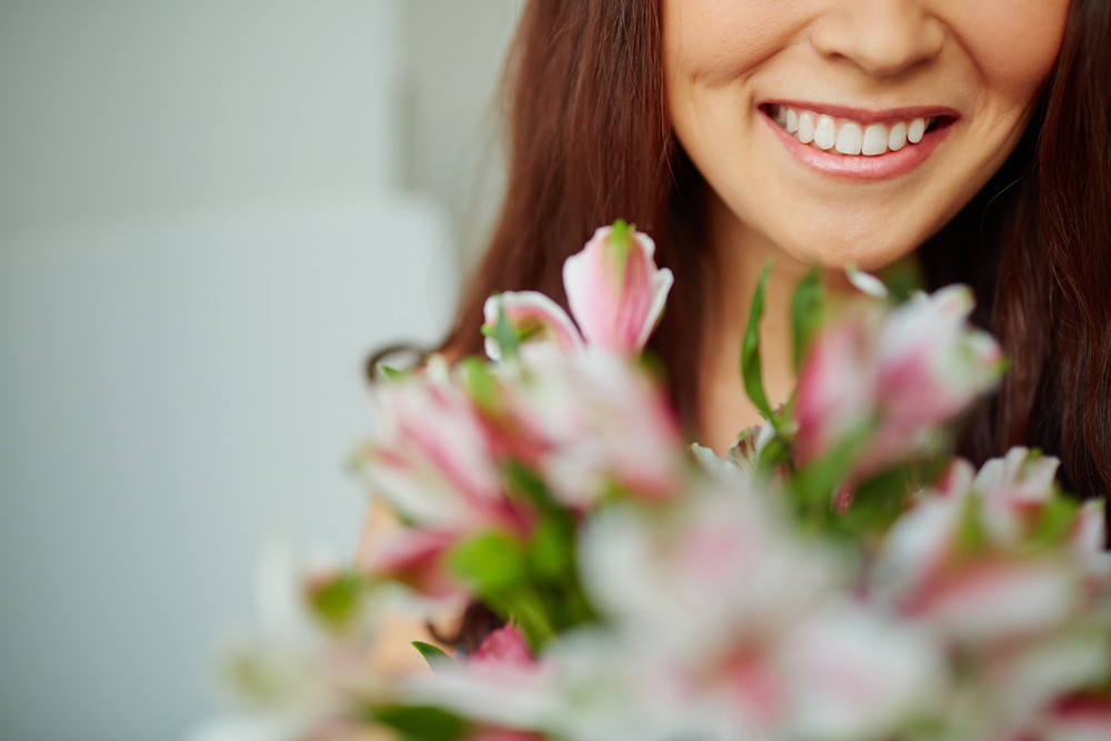 Close-up Of Female Toothy Smile And Flowers