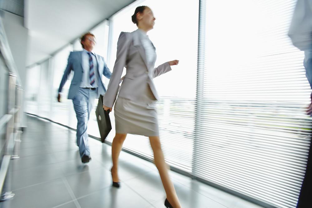 Businesswoman Walking Along Corridor With Elegant Man On Background