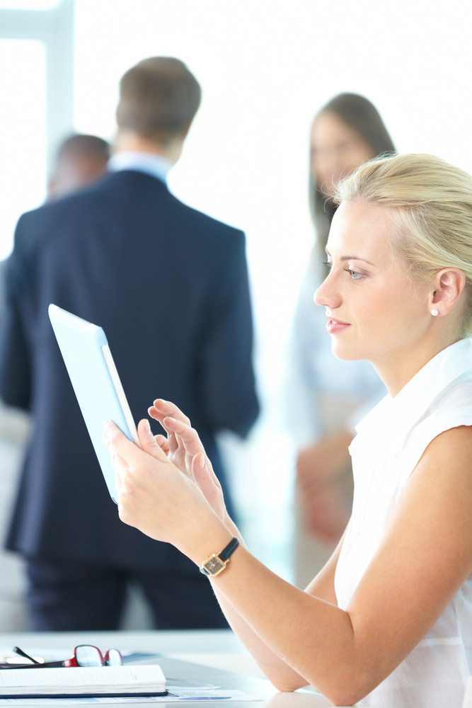 Portrait Of Pretty Businesswoman Uisng Touchpad In Working Environment