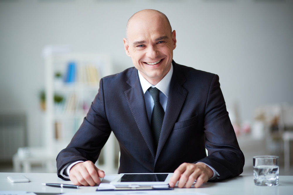 Portrait Of Elegant Businessman With Touchpad Working In Office