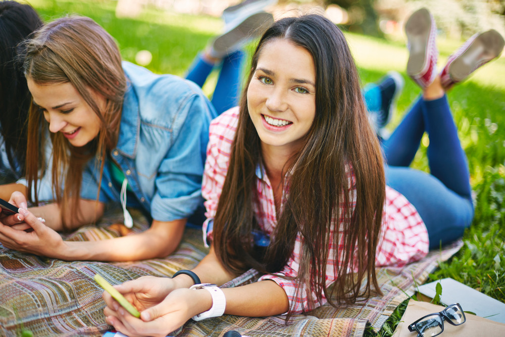 Modern Teenage Girls Using Telecommunication Technologies While Having Rest In Park