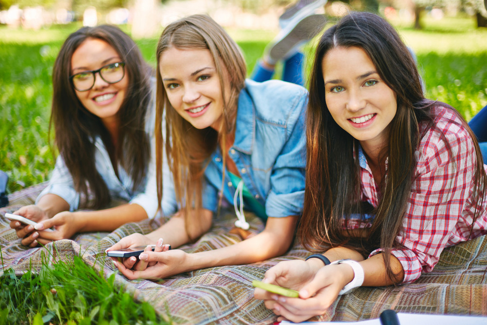 Positive Teenage Girls With Telecommunication Technologies Looking At Camera In Park