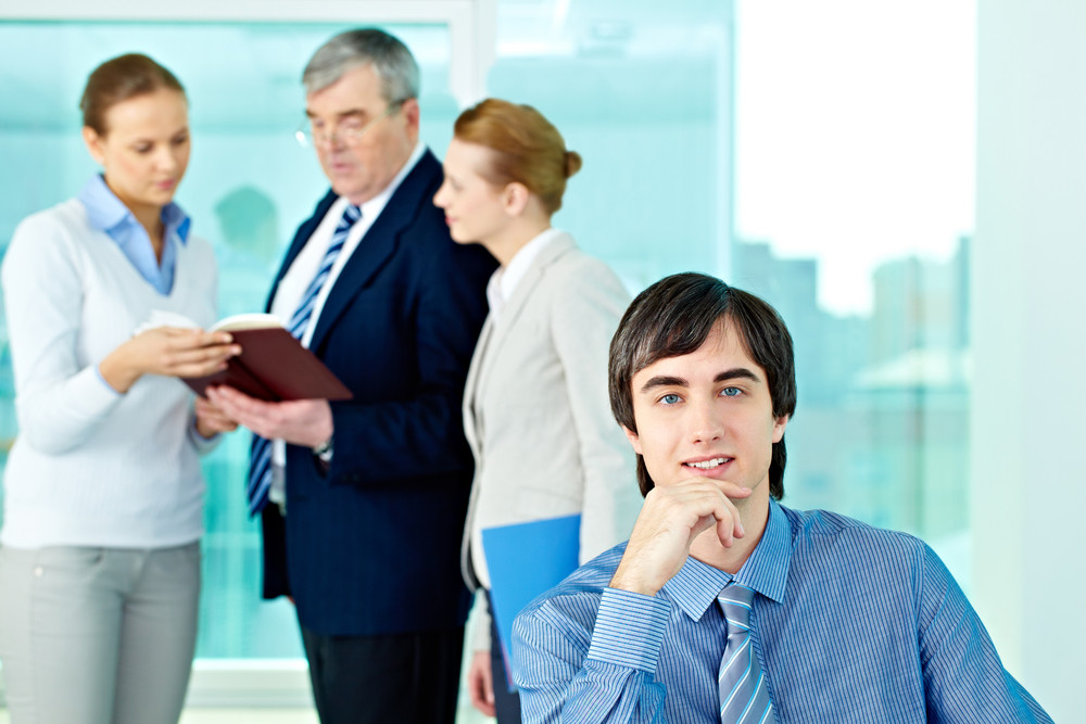 Portrait Of Confident Leader Looking At Camera With Working Employees Behind