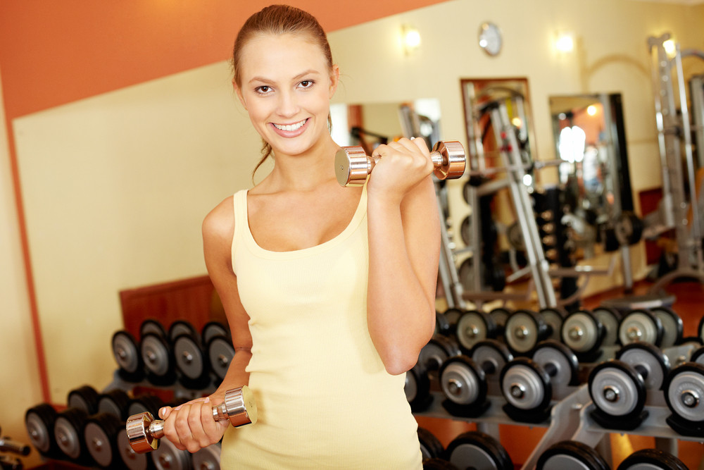 Portrait Of A Young Girl Exercising With Dumbbells