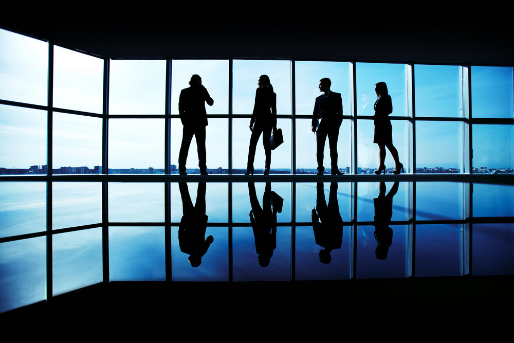 Silhouettes Of Several Office Workers Standing By The Window And Looking At Their Colleague Speaking On The Phone