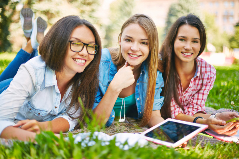 Positive Teenage Girls With Technological Devices Spending Leisure In Park