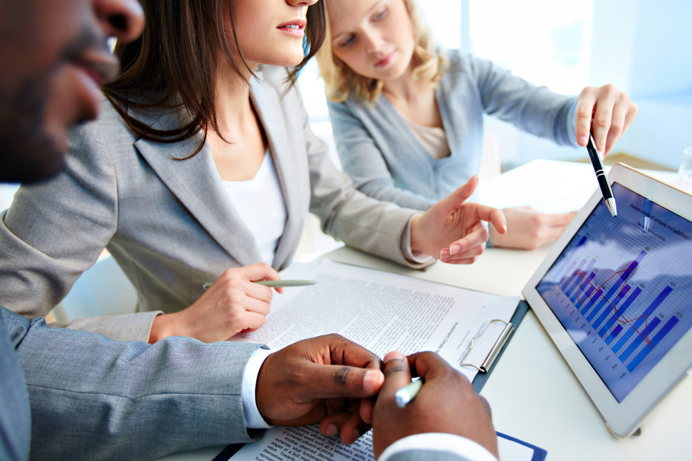 Close-up Of Young Businesswomen Discussing Document In Touchpad