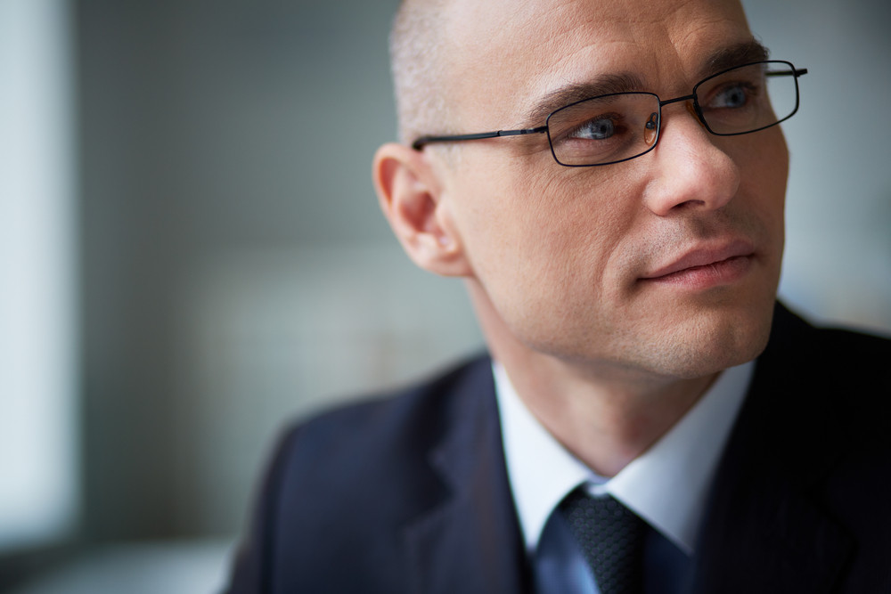 Portrait Of Attractive Businessman In Eyeglasses Looking Aside