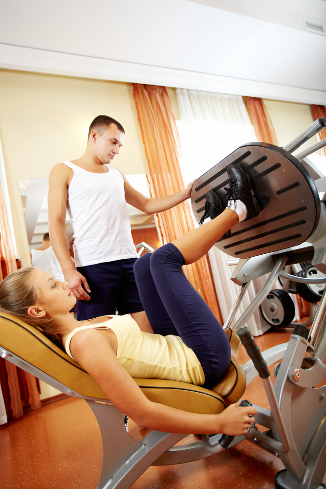 Young Woman Doing Abdominal Exercises With Training Machine