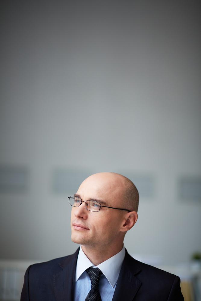 Portrait Of Pensive Businessman In Eyeglasses In Isolation