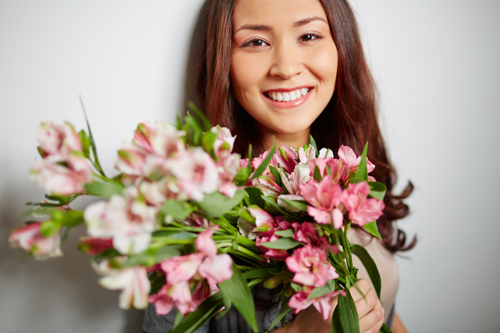 Portrait Of Beautiful Girl With Bunch Of Fresh Flowers Looking At Camera In Isolation