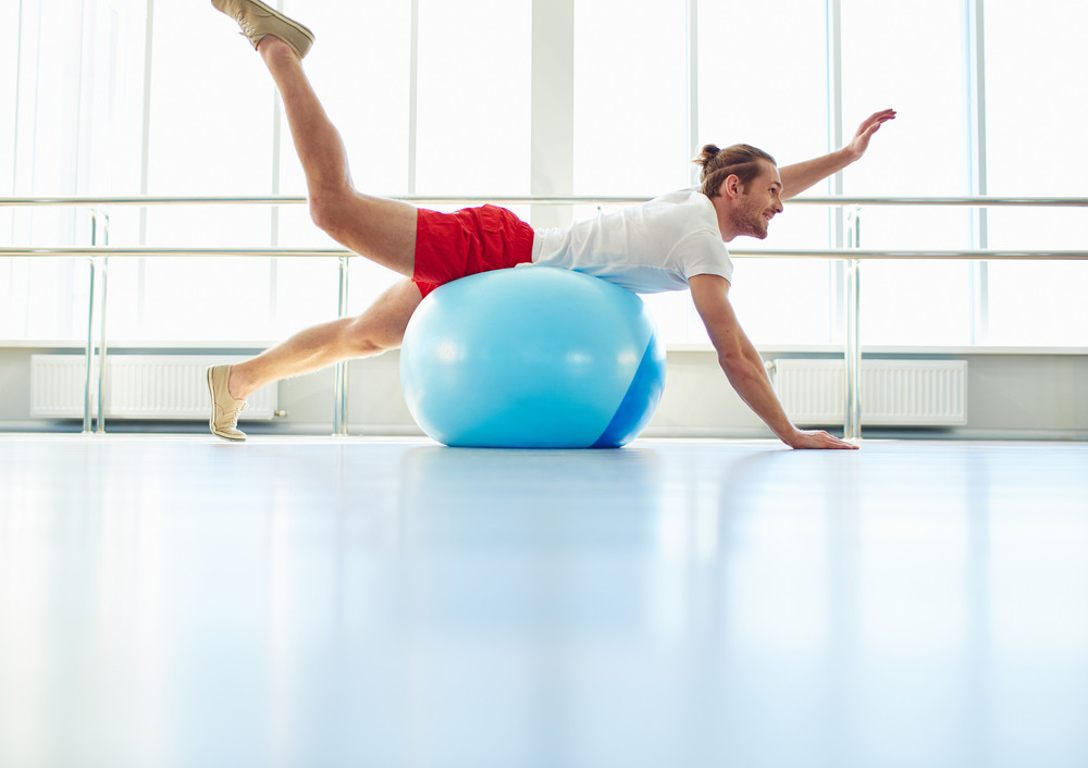 Portrait Of Young Man Doing Physical Exercise On Ball