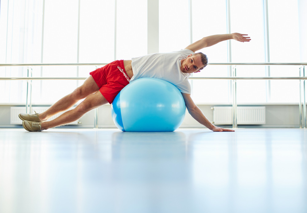 Portrait Of Young Man Doing Physical Exercise On Ball And Looking At Camera