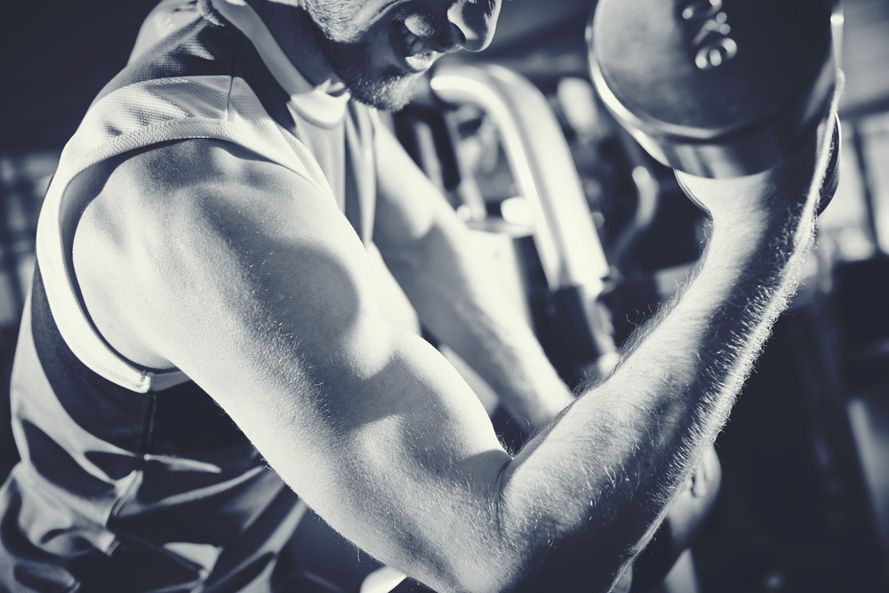 Arm Of Strong Man Doing Exercise With Barbell