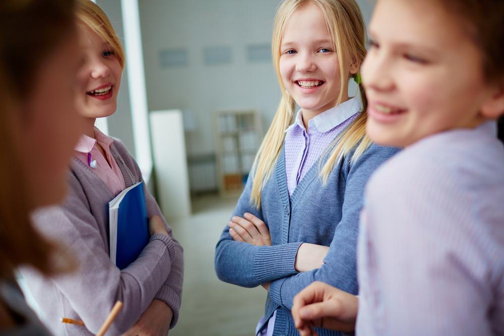 Portrait Of Three Happy Schoolgirls And Schoolboy Talking During School Break