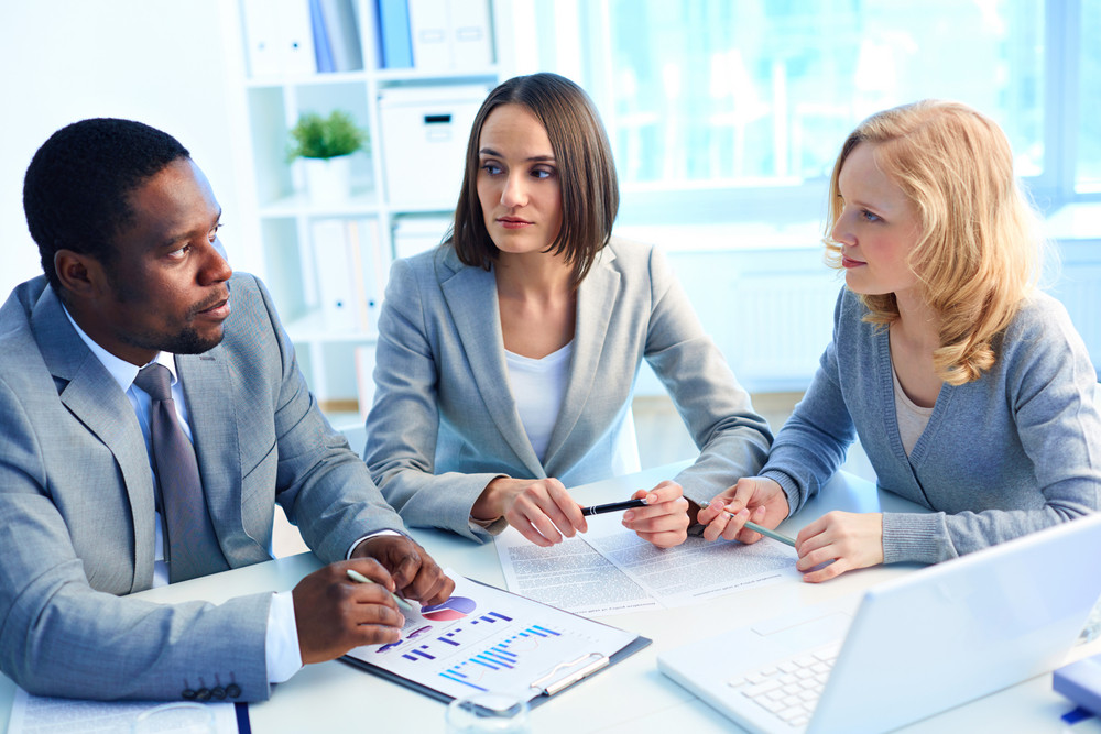 Group Of Serious Businesspeople Interacting At Meeting