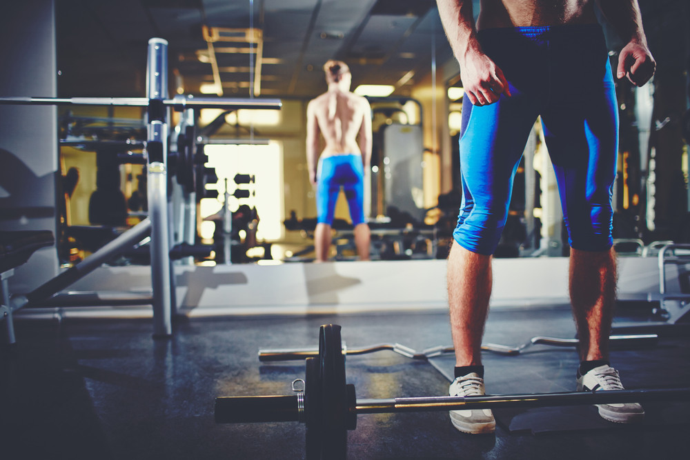 Image Of Topless Man Standing In Gym With Weight Near By