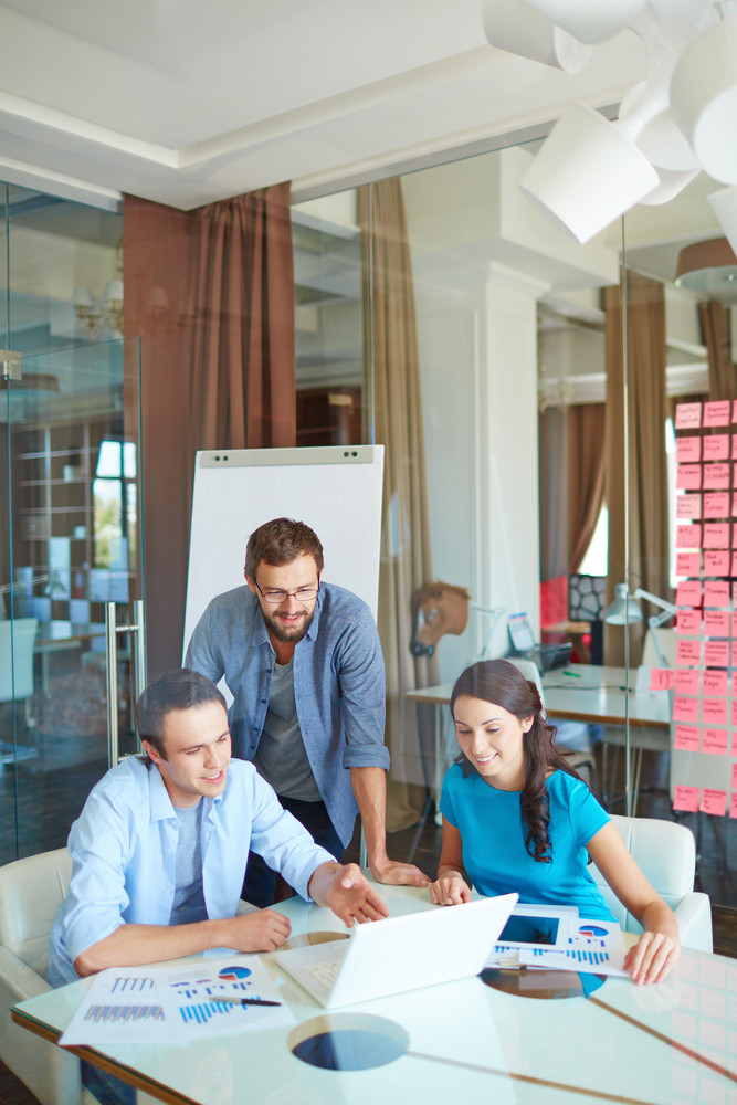 Group Of Three Successful Business Partners In Casual Looking At Laptop Screen And Listening To Young Man Explanations At Meeting In Office