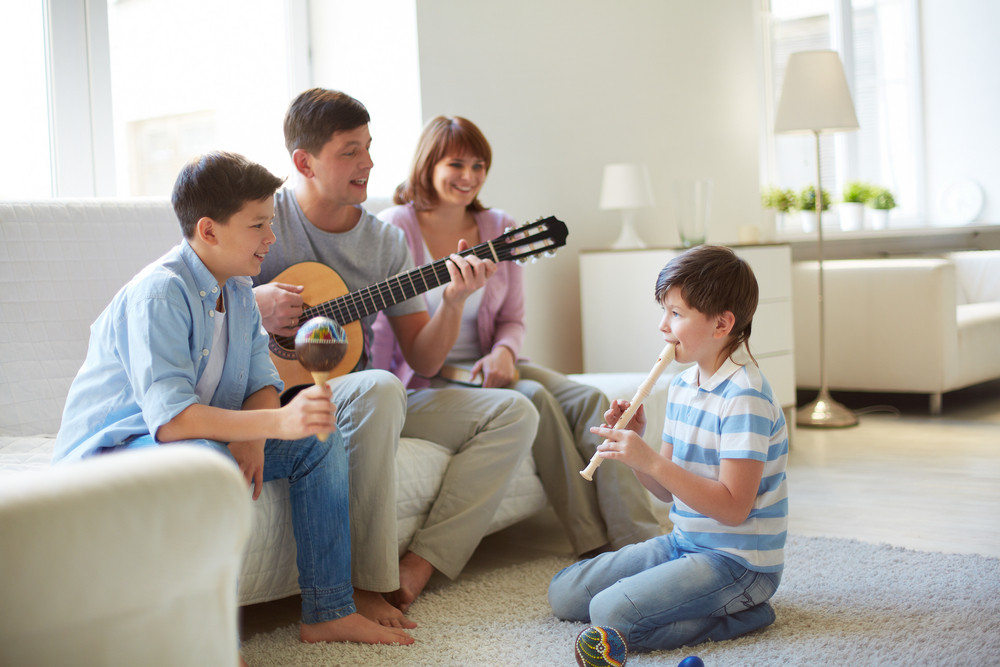 Portrait Of Handsome Siblings And Their Father Playing Musical Instruments At Home
