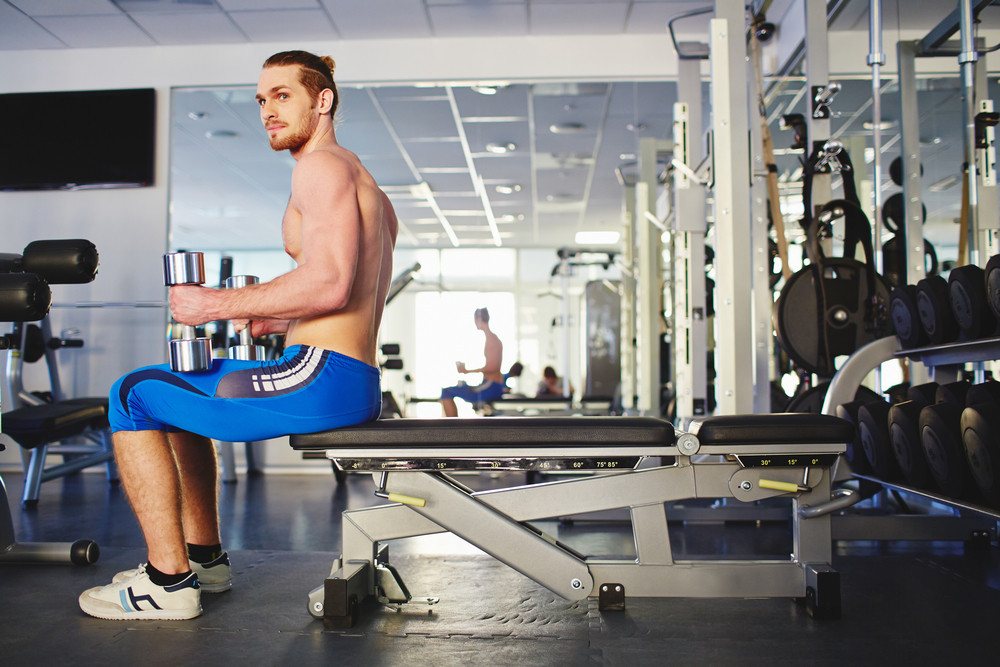 Young Man With Barbells Sitting In Gym
