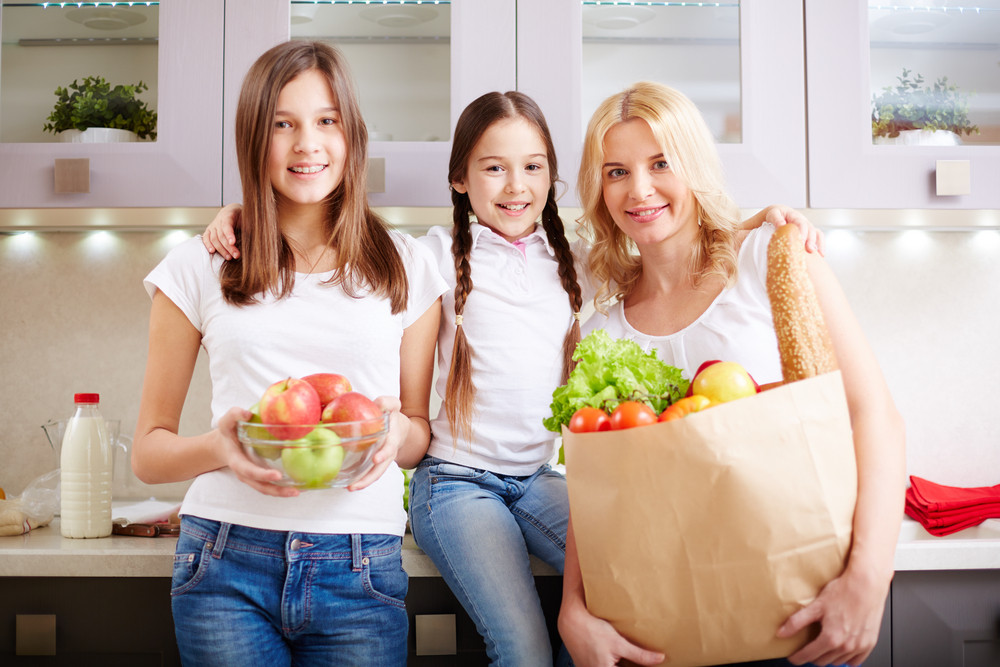 Portrait Of Happy Mother And Two Daughters Looking At Camera In The Kitchen