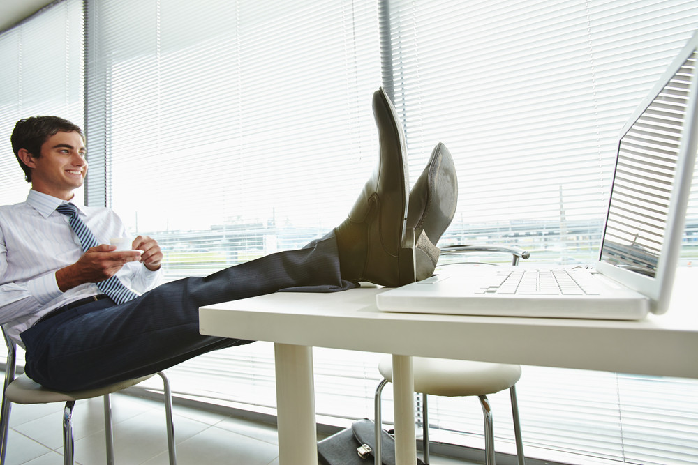 Portrait Of Happy Businessman Sitting In Office