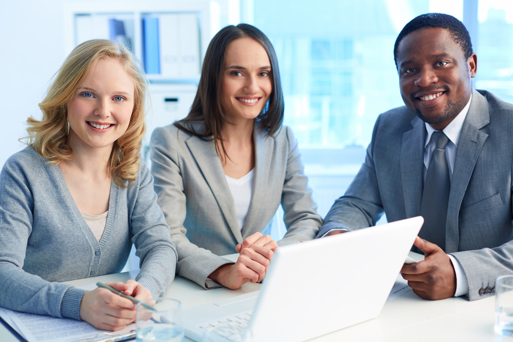 Group Of Happy Businesspeople Looking At Camera With Smiles