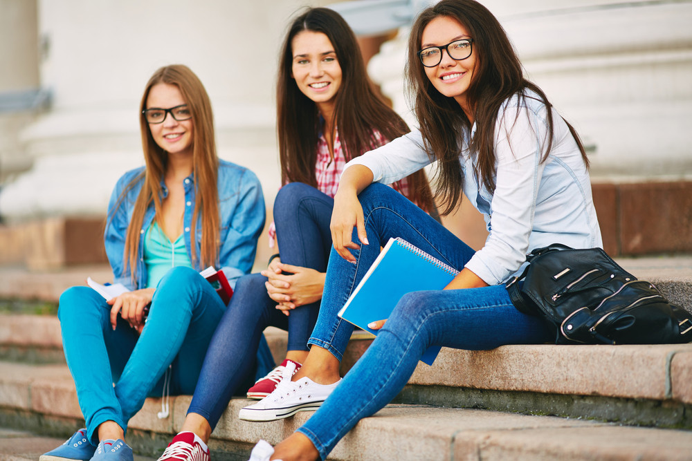 Portrait Of Cute Teen Students In Casual Sitting On Stairs Of College