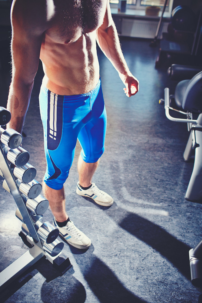 Image Of Topless Man Standing In Gym With Dumbbells Near By