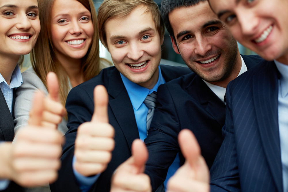 Portrait Of Five Business Partners Keeping Thumbs Up And Looking At Camera With Smiles
